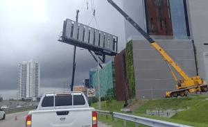 ¡De infarto! El blooper de una grúa causó la caída de una enorme valla publicitaria (VIDEO)