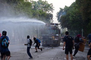 Así se vive el caos desde adentro: Manifestantes tratan de voltear a un camión de carabineros en Chile (Videos)